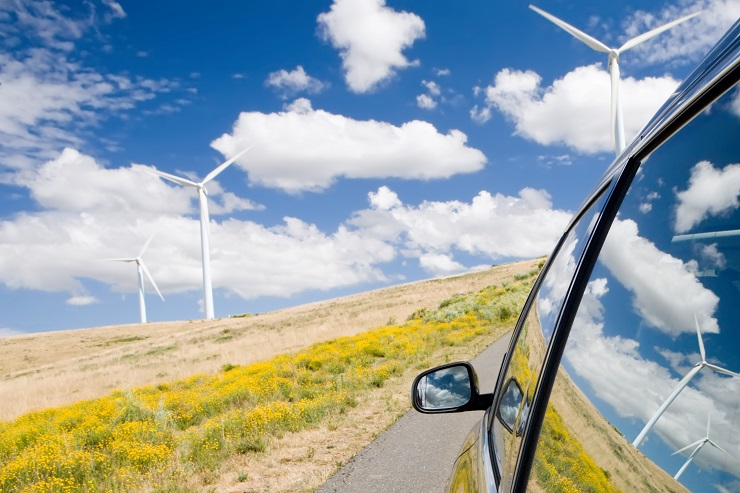 Car driving along field with windmills.