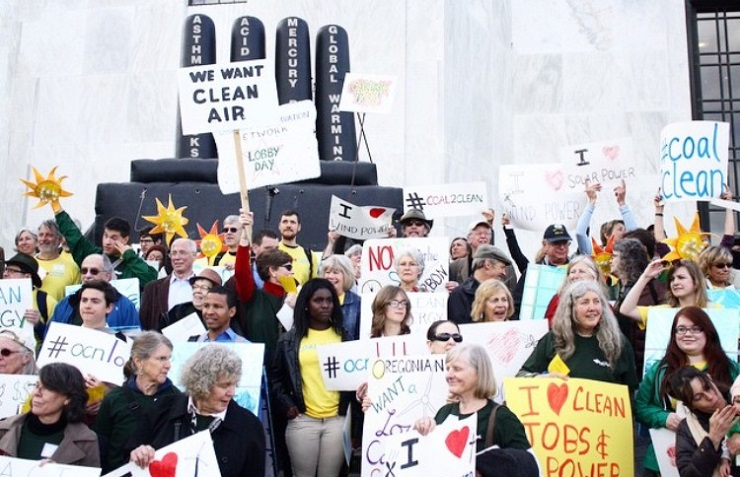 Enviros on Oregon Capital building steps with signs -- climate change lobbying.
